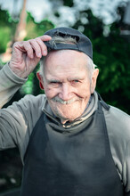 Portrait Of An Old Farmer In A Baseball Cap. The 87 - Year-old Smiles And Adjusts His Baseball Cap After Work. Active Ageing. To Close