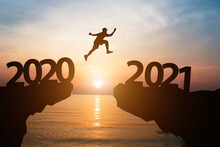 Happy New Year 2021 And Silhouette Concept , Man Jumping From 2020 To 2021 With Beautiful Orange Sky And Sea.