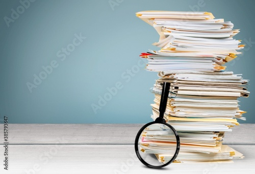 File folders with documents and magnifying glass on the desk - 385793647