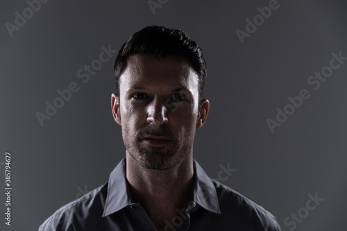 Portrait of young man against grey background