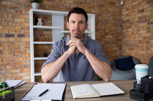 Portrait of man sitting on his desk