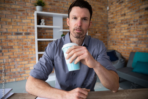 Portrait of man holding coffee cup while sitting on his desk