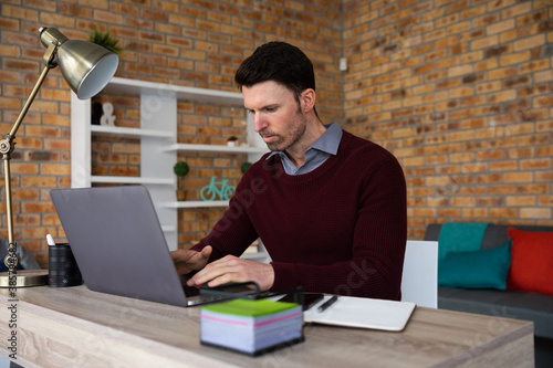 Man using laptop while sitting on his desk