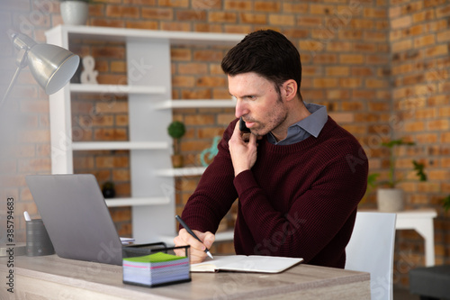 Man talking on smartphone and taking notes while sitting on his desk