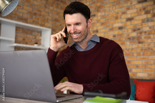 Man using laptop and talking on smartphone while sitting on his desk