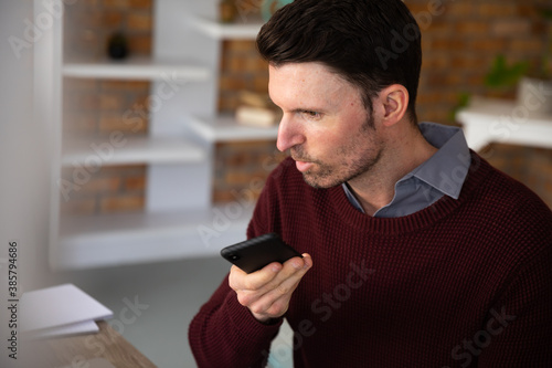 Man talking on smartphone while sitting on his desk