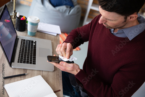 Man wiping his smartphone with tissue while sitting on his desk