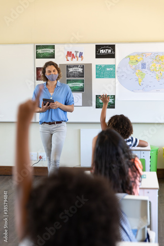 Obraz Female teacher wearing face mask holding digital tablet teaching to students in class - fototapety do salonu