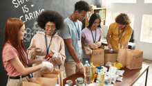 Happy Young Volunteers Group Collecting, Sorting Food In Paper Bags, Diverse Team Working Together On Donation Project In Charitable Organization Office