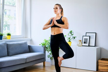Woman In Sports Clothing Practicing Tree Pose At Home