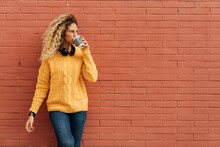 Young Blond Woman Drinking Coffee From Disposable Cup While Looking Away Against Red Brick Wall