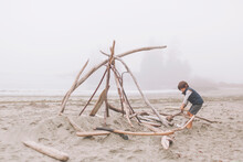 Boy Arranging Wood Logs For Ca...