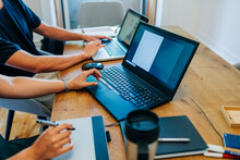 Web Designers Working While Using Laptop At Office Desk