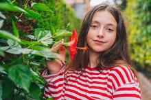 Cute Little Girl Holding Hibiscus Flower Growing In Backyard
