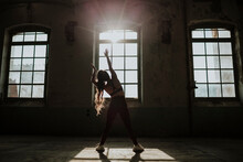 Silhouette Of Woman Exercising While Standing At Abandoned Factory
