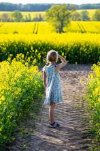 Girl Standing In Farm Of Rapeseed Field