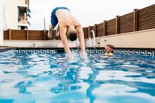 Young Man Jumping Into Pool Hi...