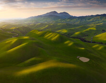 Scenic View Of Rolling Hills During Sunrise