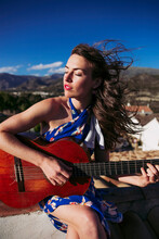 Beautiful Young Woman With Eyes Closed Practicing Guitar On Roof