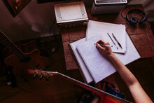 Young Woman Writing In Book While Practicing Guitar At Home