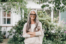 Portrait Of Smiling Woman With Long Grey Hair Wearing Spectacles Standing In The Garden