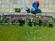 Aerial View Of Woman Sitting On Terrace In Garden
