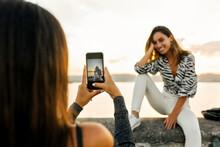 Woman Taking Photo Of Friend S...
