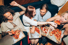 Friends Enjoying Pizza During Social Gathering At Home