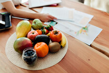 Woman's Hand Arranging Papers By Fruits Kept On Table At Home