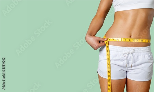 Obraz Slim young woman measuring her thin waist with a tape measure - fototapety do salonu