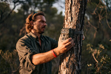 Mature Man Holding Trail Camera On Tree Trunk While Standing In Forest