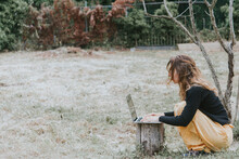 Woman Crouching While Using Laptop On Tree Stump At Park