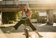 Cheerful Woman Enjoying Cycling On Street In City During Sunny Day
