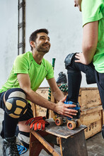 Smiling Man Looking At Son While Helping In Wearing Skate