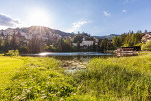 Switzerland, Canton Of Grisons, Arosa, Sun Shining Over Shore Of Untersee Lake In Summer With Town In Background