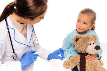 Selective focus of pediatrician in latex gloves holding cotton and syringe near child with soft toy isolated on white