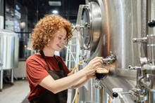 Woman Working In Craft Brewery Tapping Beer From Tank
