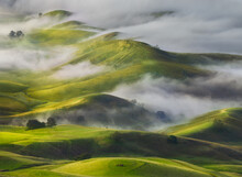 Scenic View Of Fog Over Hills During Sunrise