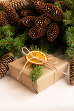 Christmas Gift In Craft Packaging Decorated With A Spruce Branch And A Slice Of Dried Orange On A Background Of Spruce Branches With Cones