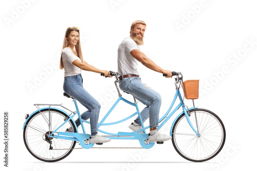 Happy couple in matching outfits riding a tandem bicycle