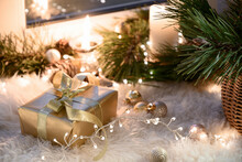 Christmas Golden Gift On Warm Windowsill With Garland, Fur, Candles, Baubles And Basket. Cozy Home. Close Up.