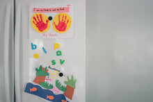 Handprint Art And Magnets On White Fridge