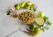 Bowl Of Tomatillo Salsa With It's Ingredients On White Quartz Counter.
