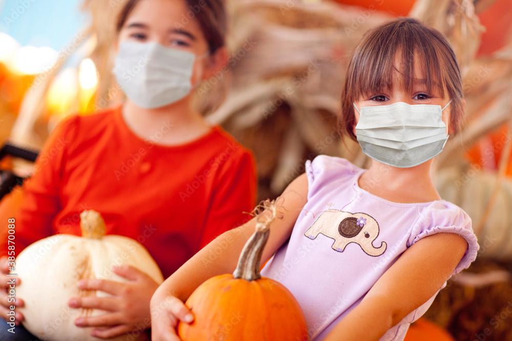Fototapeta Cute Little Girls Holding Their Pumpkins At A Pumpkin Patch Wearing Medical Face Masks