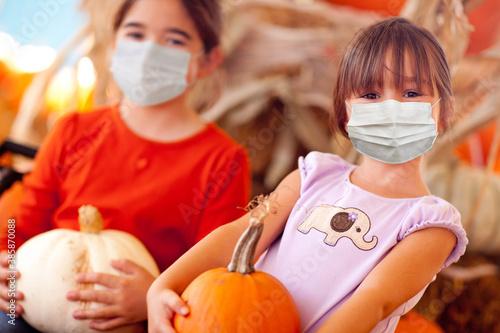 Fototapeta Cute Little Girls Holding Their Pumpkins At A Pumpkin Patch Wearing Medical Face Masks obraz