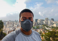 Black Man Wearing A Mask With The Center Of Rio De Janeiro In The Background.