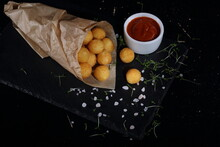 Potato Balls With Cheese Filling In Paper Bag On Black Background