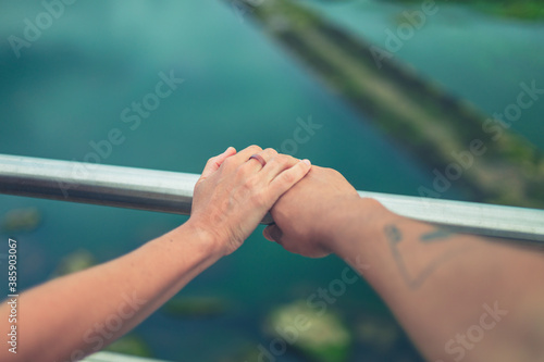 Fototapeta Young couple holding hands on railing by water