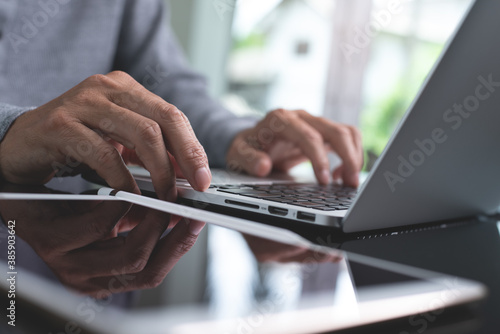 Foto Man hands typing on laptop computer surfing the internet working from home offic