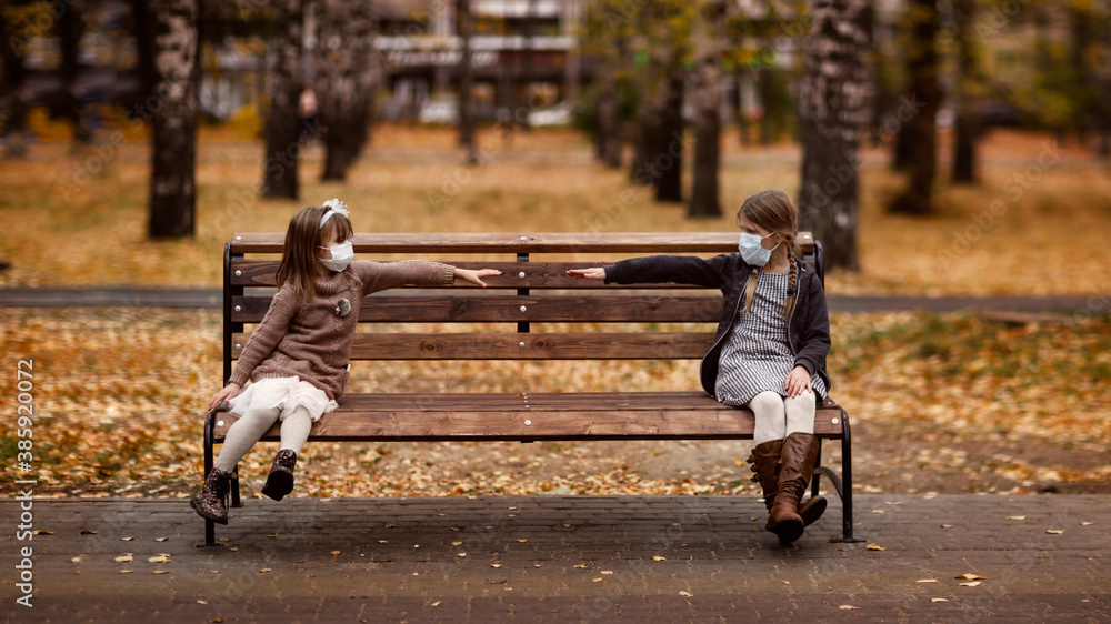 Fototapeta Children two girls friends for a walk in the park, children sit on a bench wearing masks, social distance and friendship during quarantine and restrictions